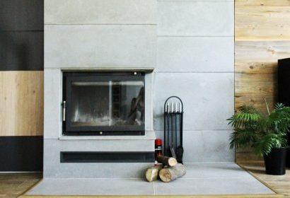 Salon z kominkiem i dekoracją ściany z płyt betonowych